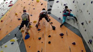 Looking up at three people climbing an indoor rock wall