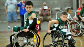 Two junior wheelchair basketball athletes back-to-back on the court