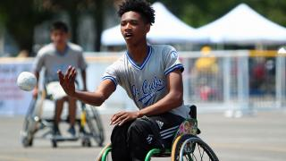Junior wheelchair softball player pitching ball