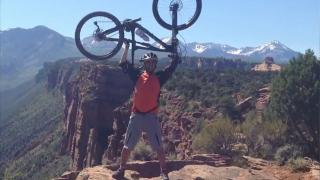 Sami - on a mountain holding a bike above his head