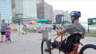 Brad the Bullet Baker riding a hand cycle on a beach in chicago