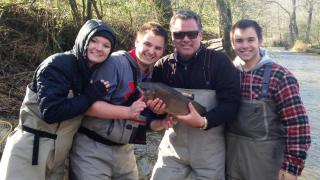 Scott and family in fishing gear holding a fish