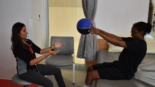 patient holds ball with hands during therapy with PT