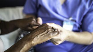 Nurse holds hands of patient