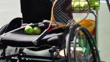 Wheelchair in foreground of tennis court. Wheelchair seat holds a tennis racket and tennis balls